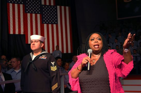carol woodsSinger_and_performer_Carol_Woods_sings_to_service_members_in_the_hangar_bay_aboard_USS_Kitty_Hawk_(CV_63)_prior_to_the_visit_by_Vice_President_Dick_Cheney